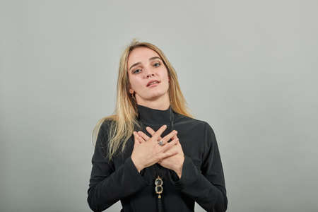 Hand on chest, busy laughing with one arm against thorax. Excited. Feels gratitude, gesture of sincere feelings from heart, love concept, demonstrates sign of affection, positive emotions, smile.