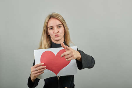 Love message on sheet, nice keeps white paper of red heart. Valentines day card. Young attractive woman, dressed black sweater with green eyes, blonde hair, background Stock fotó