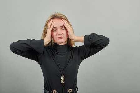 Headache grimacing pain holds the back of neck indicating location. Fatigue during workaholism labor. Young attractive woman, dressed black sweater with green eyes, blonde hair, background