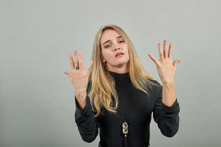 Showing ten 10 fingers hand gesture, show the number three with hands, pointing up arm while smiling confident, happy. Young attractive woman, dressed black sweater with green eyes, blonde hair