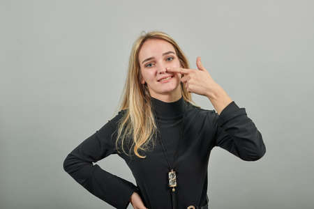 Pointing with hand at chest and staring. Shocked facial expression. Young attractive woman, dressed black sweater with green eyes, blonde hair, background