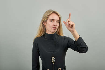 Hand points index finger up, pointing forefinger surprise gift option, great idea. Young attractive woman, dressed black sweater with green eyes, blonde hair, background