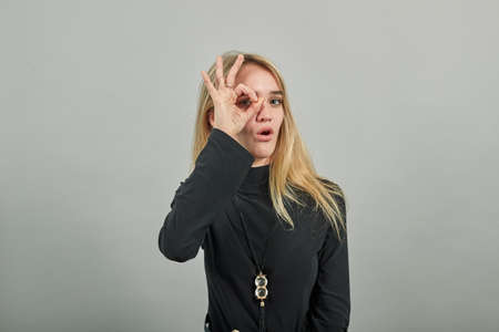 View of hand fingers showing ok sign, gesturing making okay, human emotions, facial expressions, feelings. Young attractive woman, dressed black sweater with green eyes, blonde hair, background