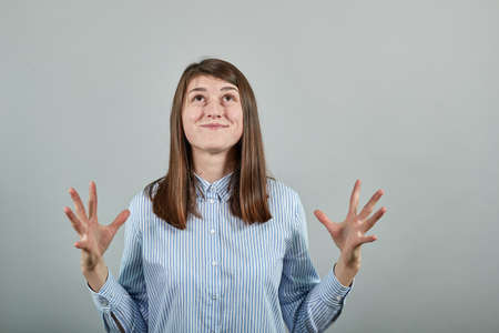 Palms up, place your product here, raising arms wide spread is catching something. Young attractive woman, dressed blue shirt with brown eyes, brunette hair, grey background