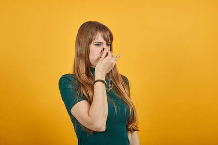 Covering nose with hand showing something stinks, isolated, hands face against, staring into the camera, eyes wide open, two fingers. Pinches snout looks, disgust bad smell sign. Young attractive