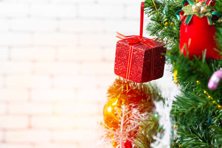 A red gift box hanging on a Christmas tree. Ideas to welcome the upcoming Christmas season.