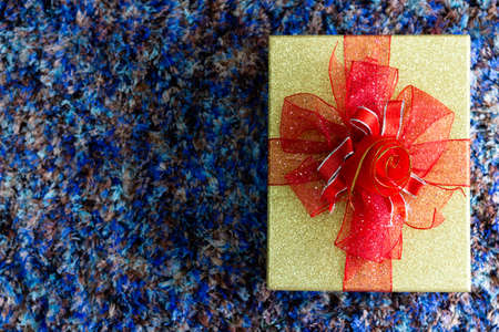 A gift box for someone special, tied with a ribbon, placed on the floor Ideas to welcome the upcoming Christmas season.