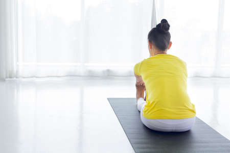 A beautiful Asian woman is exercise yoga in the yoga room for good health and flexibility of the muscles with feel good and happiness. It is a lifestyle activity healthy for everybody.