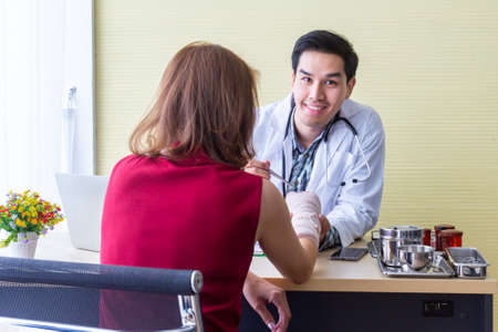 The doctor is interviewing the symptoms of Asian female patients. About broken arm for diagnosis Next time treatment With modern medicine in the medical room.