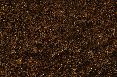 fertilizing: Brown, fertile, sandy soil ready for planting or fertilizing. Camera from above, top view. Natural background for advertisements.