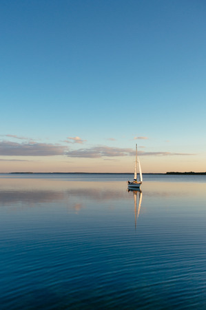 Sailing boat on a calm lake with reflection in the water. Serene scene landscape. Vertical photograph. Stock Photo
