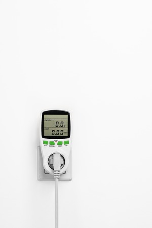 power meter: Electric power consumption meter isolated on white wall. Power saving concept or background.