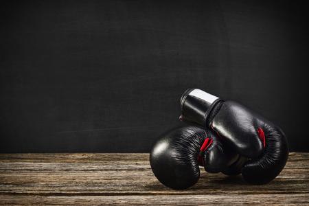 Paio di guantoni da boxe su una scrivania in legno d'epoca con sfondo di lavagna. Immagine concettuale, l'idea di una concorrenza brutale. Archivio Fotografico - 62612168