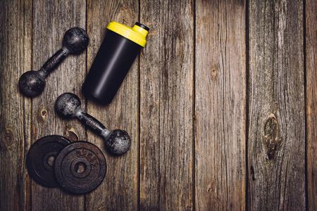 isotonic: Old iron dumbbells or exercise weights with extra plates on an old wooden deck, floor or table. Image taken from above, top view. A lot of copy space around product