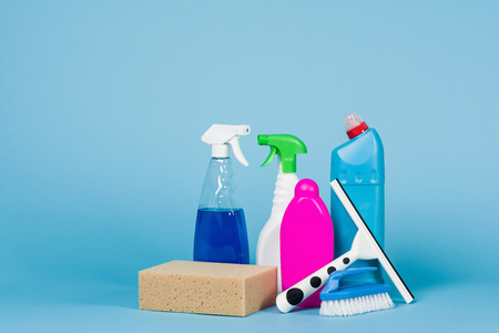 dish washing gloves: Cleaning concept - mixed detergents and cleaning accessories isolated on blue seamless background.