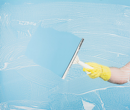 Cleaning conept - hand cleaning glass window pane with detergent and rubber aluminium wiper