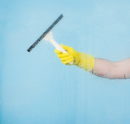 conept: Cleaning conept - hand cleaning glass window pane with detergent and rubber aluminium wiper