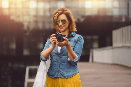 red haired woman: Woman photographer traveling trip photography concept. Red haired woman in casual clothing, jeans holding an amateur digital DSLR camera.