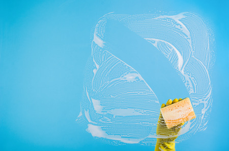 conept: Cleaning conept - hand cleaning glass window pane with detergent and wipe or rag