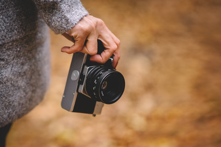 Woman hand with retro analog film camera. Concept for travel, wanderlust, outdoor adventure. Natural fall, defocused, bokeh background. Shallow depth of field Stock Photo