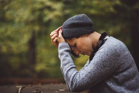 Portrait de triste, femme déprimée assis seul dans la forêt. Solitude ou concept de dépression. Millenial traiter les problèmes et les émotions. Banque d'images - 65224838