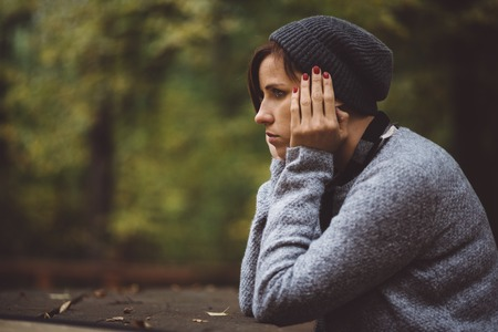 Portrait of sad, depressed woman sitting alone in the forest. Solitude or depression concept. Millenial dealing with problems and emotions. Stock Photo