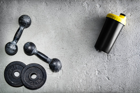 Fitness or bodybuilding concept background. Product photograph of old iron dumbbells and shaker on grey, conrete floor in the gym. Photograph taken from above, top view with lots of copy space Zdjęcie Seryjne