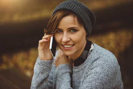 Portrait of smiling and happy young millenial woman sitting alone in the forest and talking with smartphone. Stock Photo