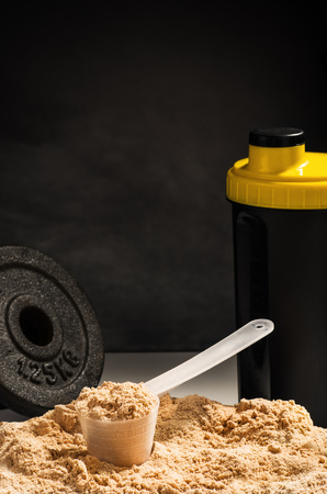 whey: Product photograph of spoon or measuring scoop of whey protein on black chalkboard background