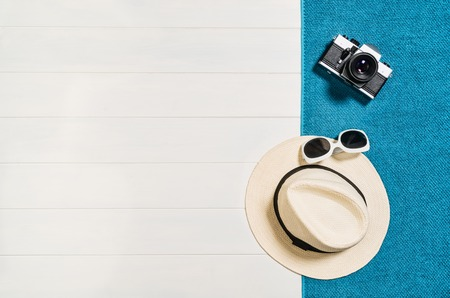 Top view of beach summer accessories with copy space. Lay flat holiday fashion background on white wooden table or floor. Horizontal frame for spa or wellness concept. Reklamní fotografie