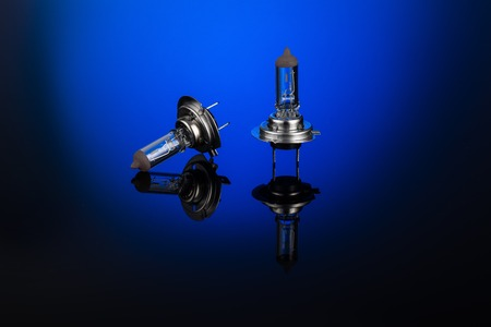 metal filament: Halogen car headlight bulb H7 or H4 on gradient background with mirror reflection