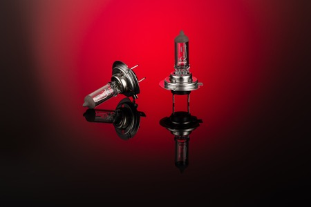 xenon: Halogen car headlight bulb H7 or H4 on gradient background with mirror reflection