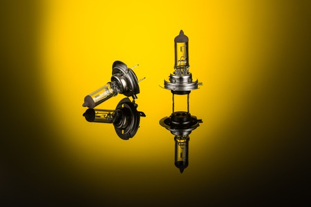Halogen car headlight bulb H7 or H4 on gradient background with mirror reflection