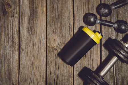 wood floor background: Old iron dumbbells or exercise weights and protein shaker bottle outdoor on an old wooden deck, floor or table in the gym. Image frame taken from above, top view. A lot of copy space around product