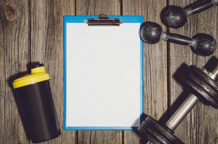 Fitness training plan of personal trainer with old iron dumbbells or exercise weights outdoor on an old wooden deck, floor or table in the gym. Image frame taken from above, top view.
