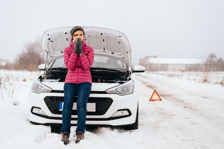 Jonge vrouw te wachten voor hulp of assistentie nadat haar auto pech in de winter. Uitgesplitst naar de auto met open kap op een landweg. Stockfoto