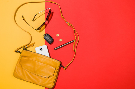 Womans accessories flat lay on colorful background. Top view. Red and yellow pastel colors with copy space around products. Horizontal image or photograph.