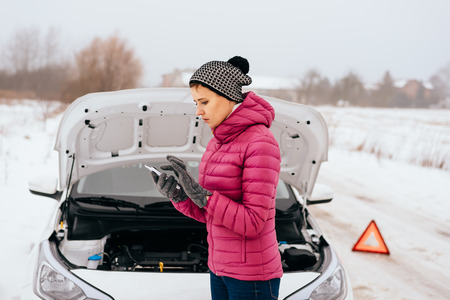 Young woman calling for help or assistance after her car breakdown in the winter. Broken down car with open hood on a country road. Stock Photo