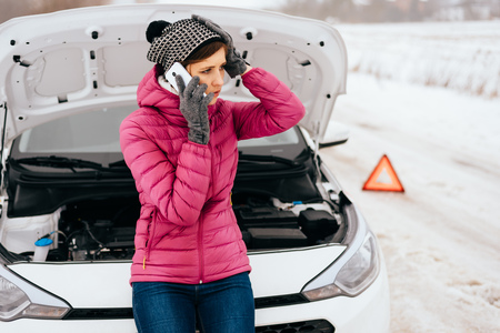 Young woman calling for help or assistance after her car breakdown in the winter. Broken down car with open hood on a country road. Zdjęcie Seryjne