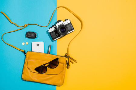 Womans accessories flat lay on colorful background. Top view Blue and yellow pastel colors with copy space around products. Horizontal image or photograph.