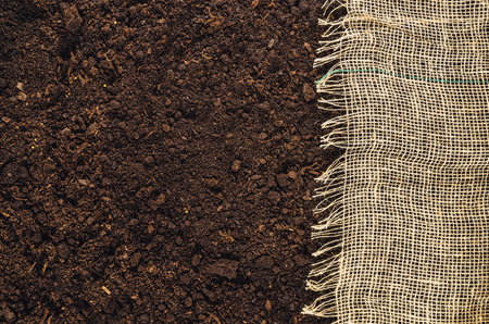 turf pile: Fertile soil texture background with jute or linen cloth seen from above, top view. Gardening or planting concept with copy space. Natural pattern