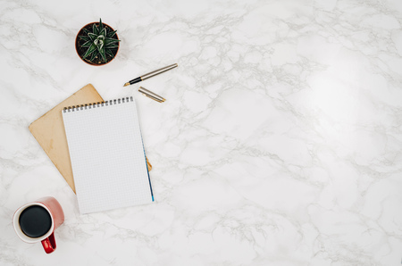 흰색 대리석 테이블 배경에 빈 노트북 페이지입니다. 위에서 찍은 이미지, 상위 뷰. 복사 공간이있는 프레임 구성