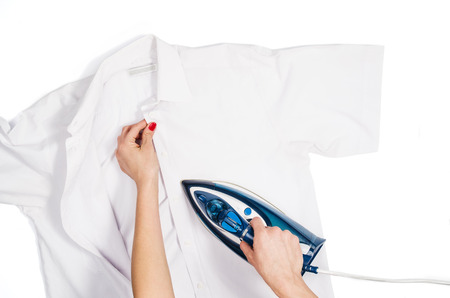 Female hand ironing clothes top view isolated on white background. Young woman with iron ironing mans shirt seen from above during housework. Blue iron on white table.