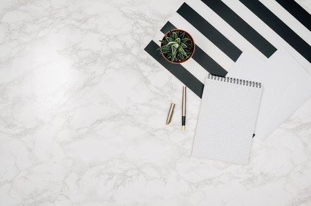 Blank notebook page on white marble table background. Image taken from above, top view. Frame composition with copy space Zdjęcie Seryjne