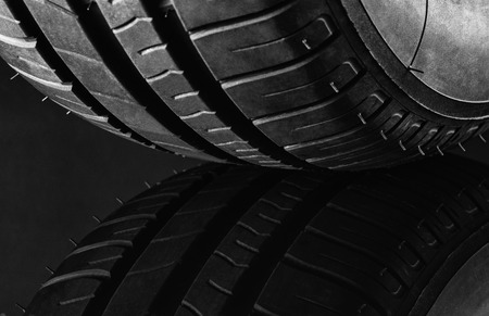 contrasty: Studio shot of a set of summer, fuel efficient car tires on black background. Contrasty lighting and shallow depth of field