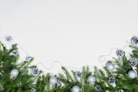 Christmas background frame top view on white wooden plank table background with copy space around products. Decorations isolated on white. Horizontal composition.