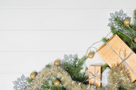 Christmas background frame top view on white wooden plank table background with copy space around products. Presents and decorations isolated on white. Horizontal and diagonal composition.