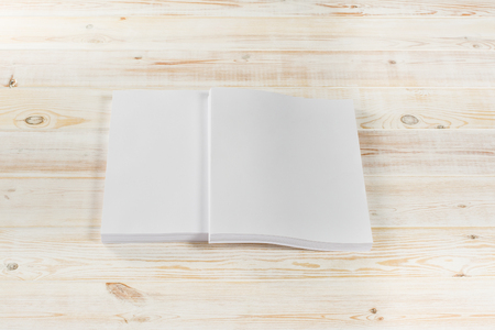 Mockup of magazine, poster, A4 brochure, catalog or flyer isolated on white wooden background. Blank page top view for use in design, mockups and simulations. Zdjęcie Seryjne