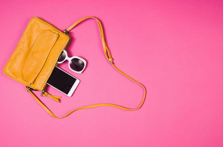 Womans accessories lying flat on pink paper table background. Pastel colors with copy space around products . Image taken from above, top view. Minimal style with room for text