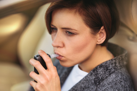 Young millennial woman using breath alcohol analyzer in the car.